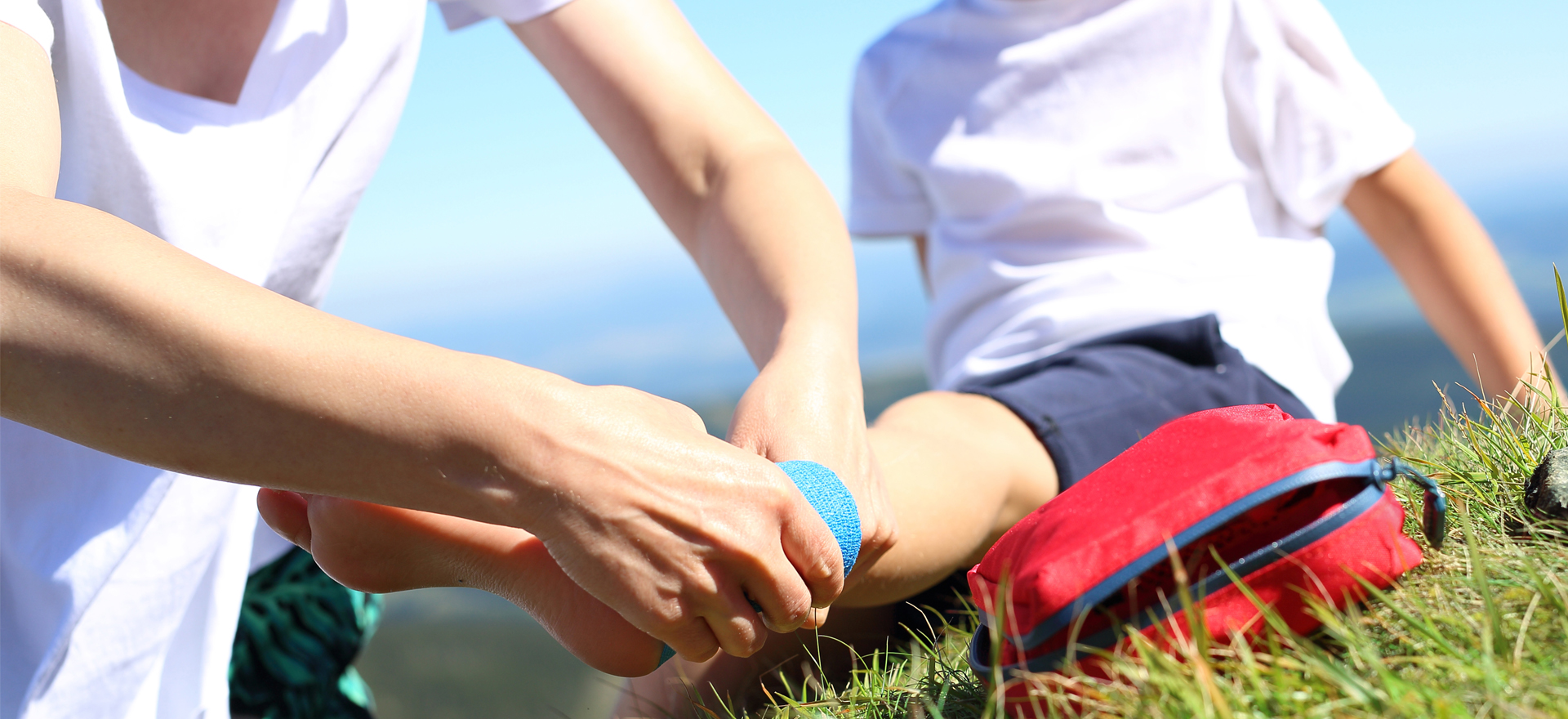 woman helping bandage child's ankle on a mountain | pacific medical supply salem