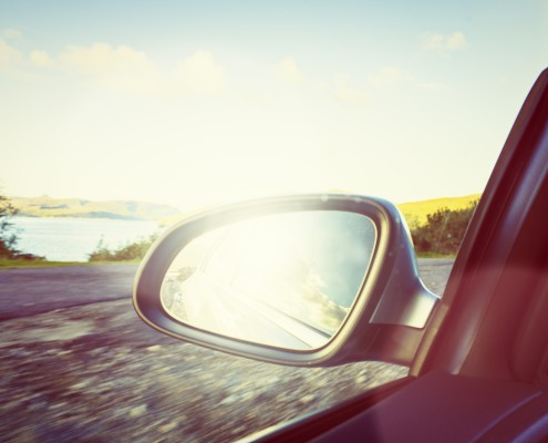 Rear View Mirror reflecting the sun driving by a lake in Scotland.
