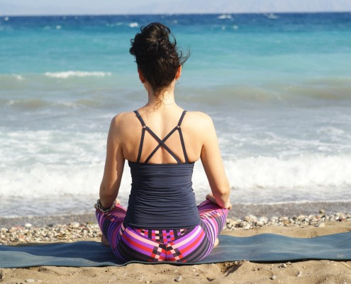 Woman sitting on yoga mat with good posture - facing the ocean on the beach