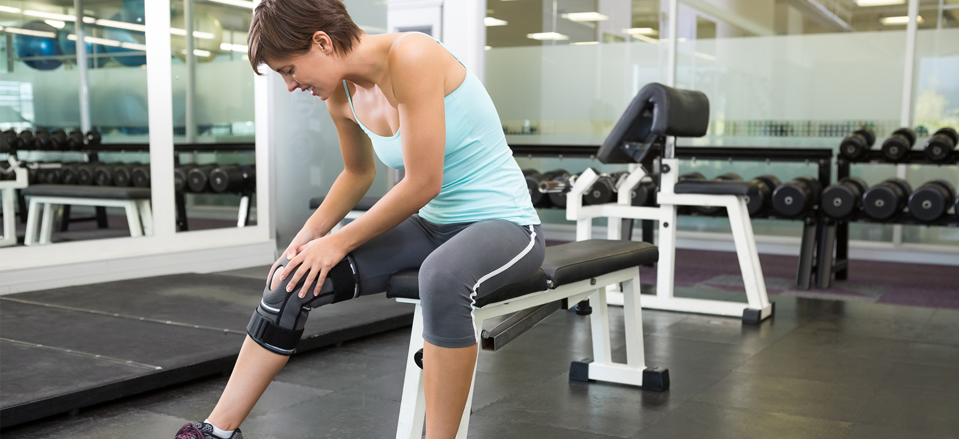 woman tending to her knee brace at the gym | pacific medical supply salem