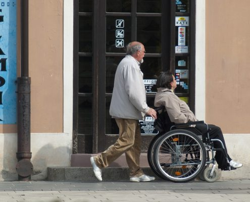 man pushing woman in wheelchair on sidewalk - caregivers