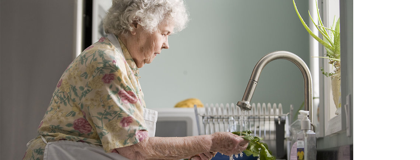 Elderly woman in kitchen washing vegetables over sink - maintaining independence