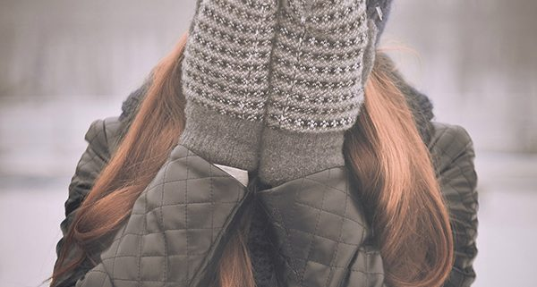 Girl in winter clothes covering her face with sad vibe
