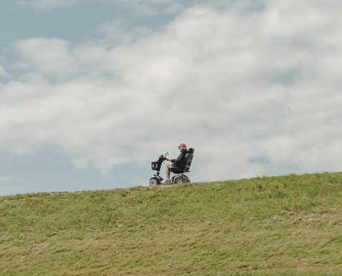 Senior Riding Motor Scooter by green fields under blue sky