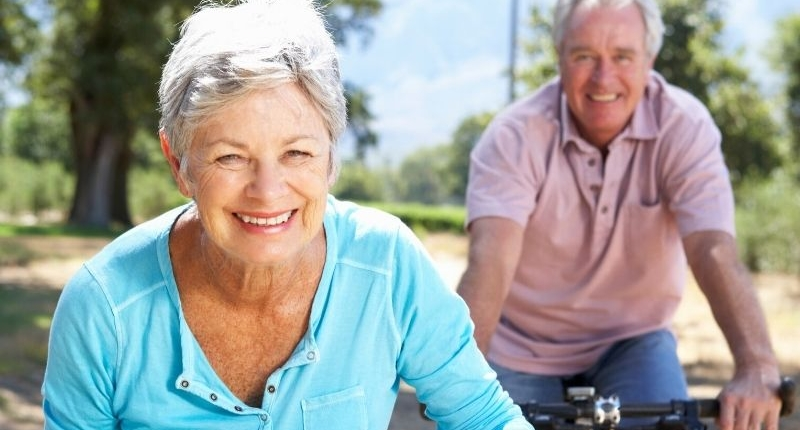 Seniors riding bicycles outside smiling on a sunny day
