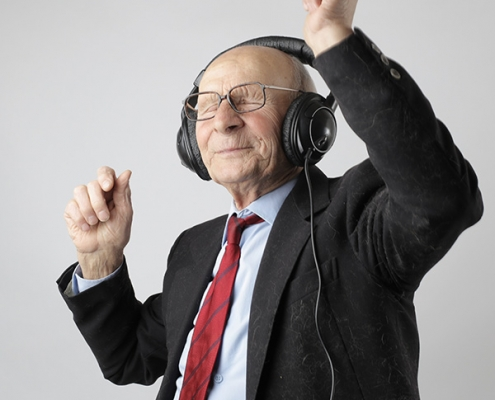 Senior in black suit dancing with headphones on