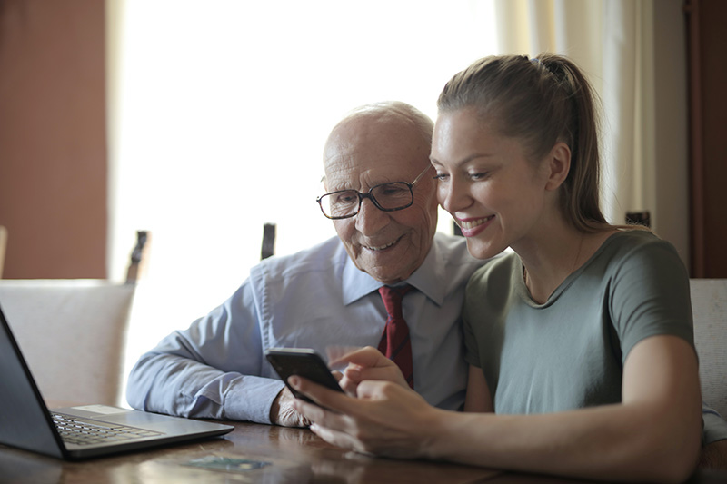 Young lady showing photos on smartphone to grandpa with laptop nearby both people are smiling