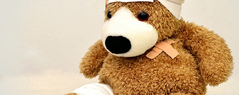 Teddy bear with bandages on his head, around one leg and two bandaids over his heart